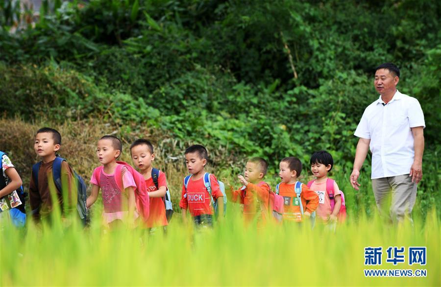 杨家洼小学老师王福hgej01平(左)和孩子们走在村里的路上